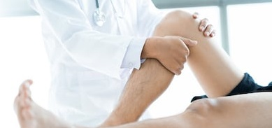 closeup male physiotherapist massaging leg 260nw 563835037